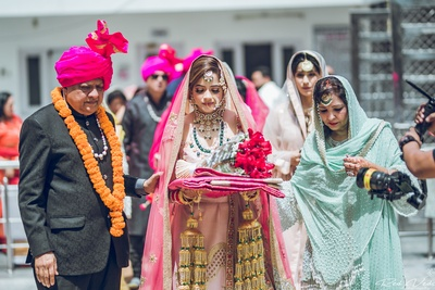bride entering the wedding ceremony in a beautiful pastel pink lehenga