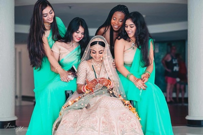Bride and bridesmaid pose for a candid photo in co-ordinated wedding sarees