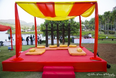 Open air decor ideas for wedding functions. Yelllow and red drapes, bolsters and mat for seating arrangement