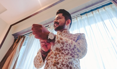 Now, one of the groom getting ready in a white and gold sherwani for the wedding ceremony.