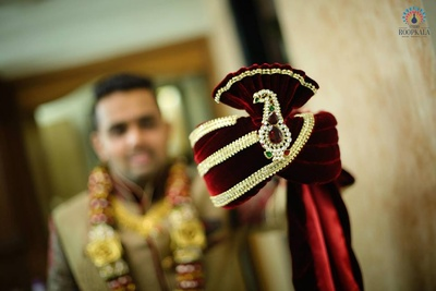 Maroon velvet Safa embellished with gold kinaari and an ornamented Kalgi