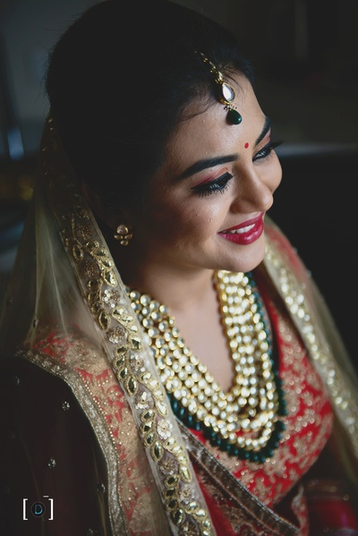 The bride done up in her makeup and jewellery, looking like royalty !