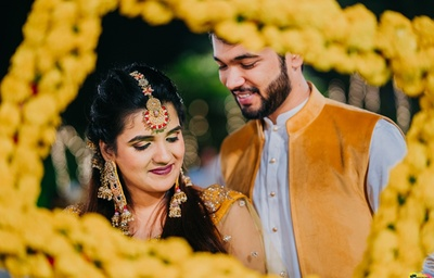 Romantic picture of the couple in a genda phool frame at the haldi