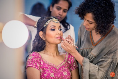 Bride getting ready for the wedding ceremony in her pink lehenga and fresh, natural makeup