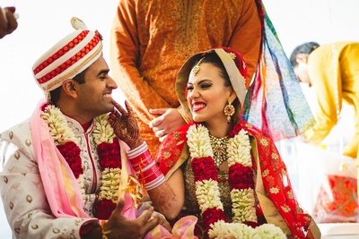 Cute wedding couple decked up in beautiful flower garlands.