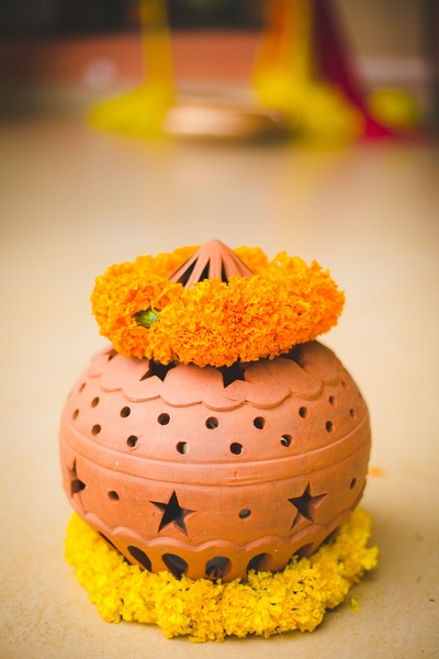 Cutout designed pot made of earthen clay decorated with marigold flower strings