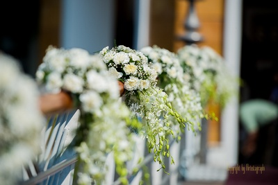 Wedding venue decorated with foral tie backs made with white Carnations and white Gladuli