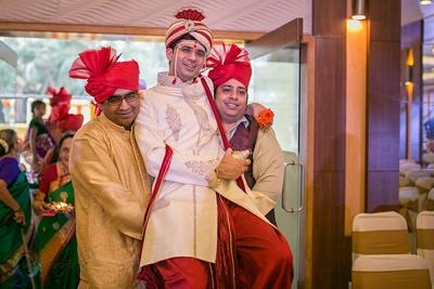 Ivory sherwani styled with maroon dhoti and a matching Safa and crush dushala