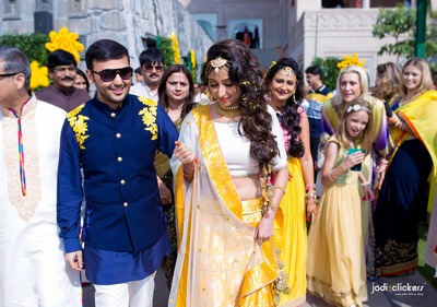 Dressed in a combination of yellow and blue outfits for their outdoor yellow themed mehndi ceremony