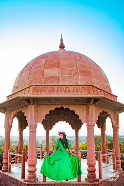 The bride possing in a parrot green lehenga against a beautiful palace backdrop.