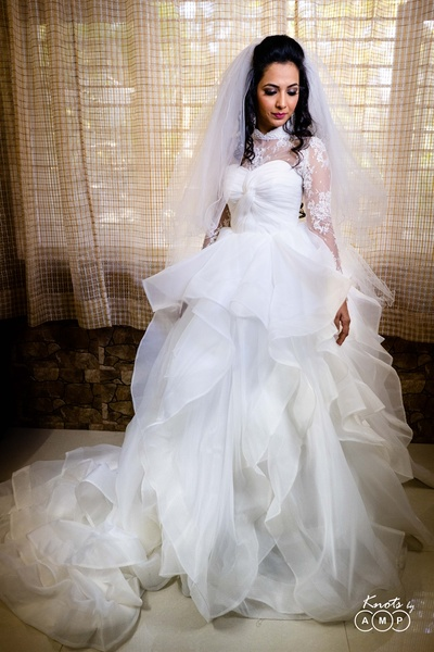 the bride looking gorgeous in a white gown with ruffles
