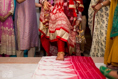 Bride in a red and white anarkali with a dull gold border and kalire