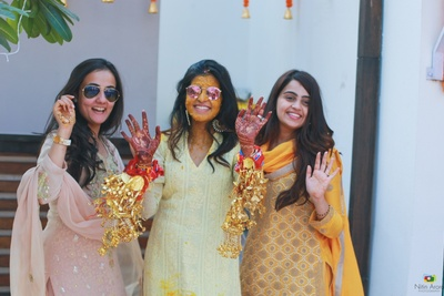The bride posing with her bridesmaids at her haldi