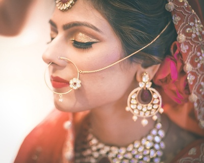 Vibrant bridal makeup styled with a floral pendant studded dainty gold nose ring