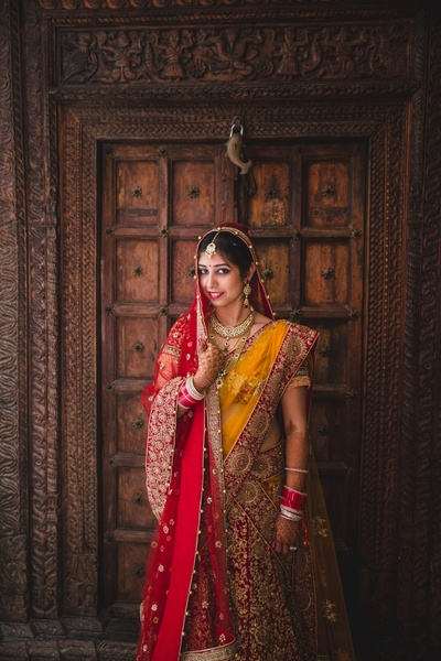 Wearing blood red lehenga with golden zardozi work paired with chrome yellow and red dupatta styled with minimal kundan jewellery.