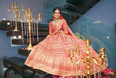 The bride posing in a beautiful scarlet lehenga