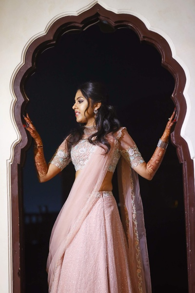 the bride posing in a blush pink lehenga at her sangeet ceremony