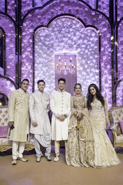 the bride and groom with their family at the reception