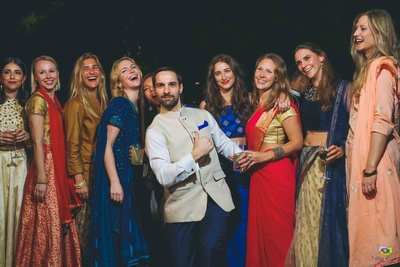 The groom poses with the bridesmaids during the sangeet ceremony