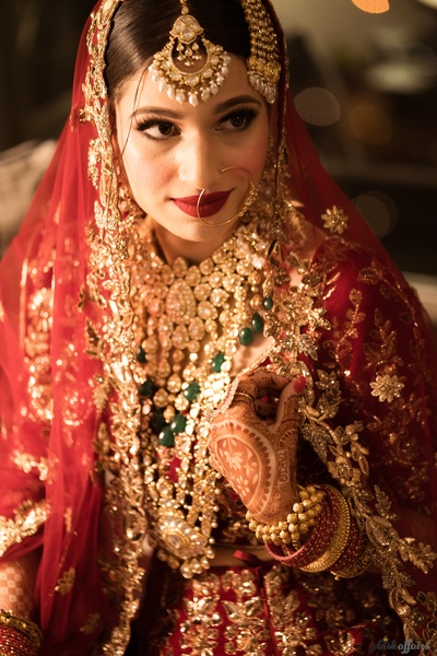 Thr bride has adorned a beautiful gold and green choker, paired with a raani haar.