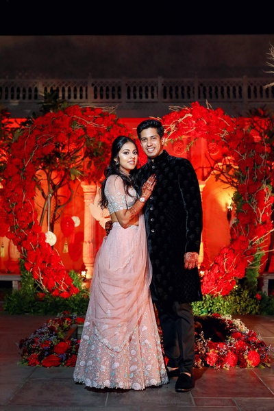 the bride in groom in contrasting outfits at the sangeet ceremony
