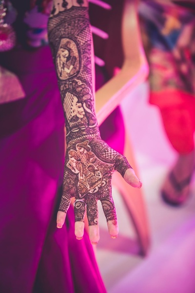 Hand filled with intricate bridal mehendi design with beautifully done bride and groom motifs.