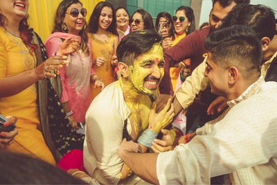 Groom ceremonial wedding photography of the haldi function with this friends and family