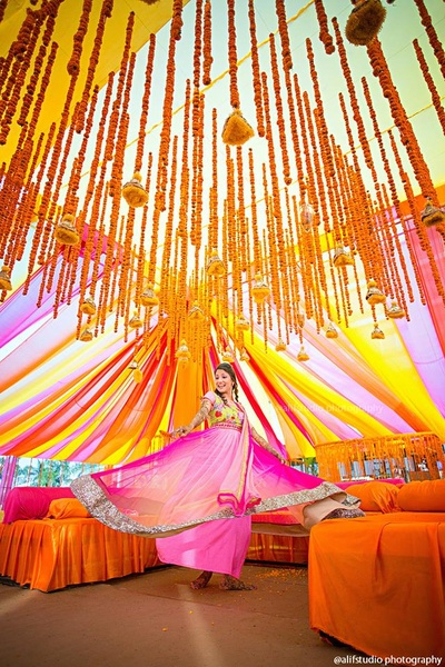 Vibrant decor with bolsters, multi colored drapes and Marigold strings with ornated ends