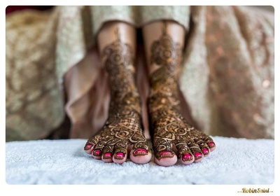 Feet covered in intricately patterned mehendi designs, styled with pink nails