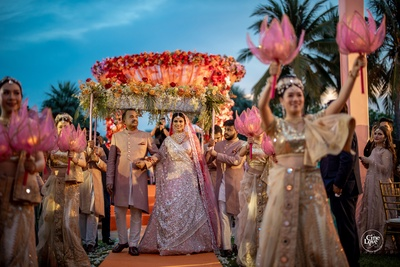 the bride walking down the aisle with her father under a phoolon ki chadaar