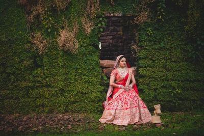 Bridal photography in regal red and gold Sabyasachi lehenga.