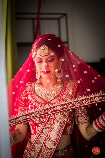 The bride in a red lehenga posing for the camera