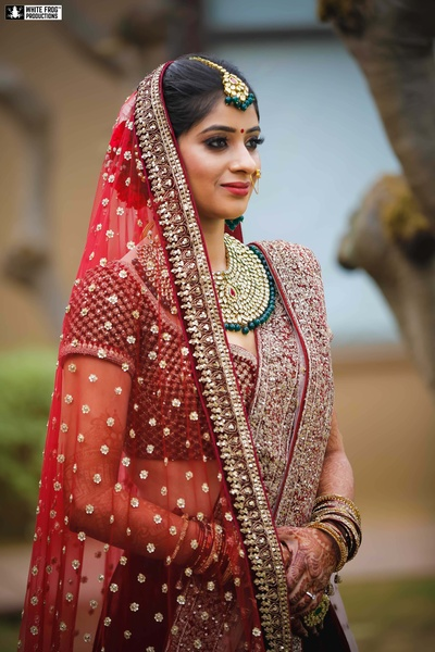 The bride looks stunning in a traditional red embellished lehenga paired with kundan jewellery.