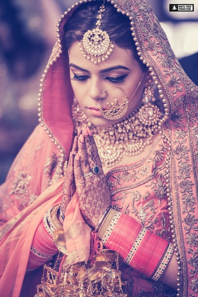 Bridal shot of the final  ceremony. The bride's flawless make is joined by pink bangles and gold nath.