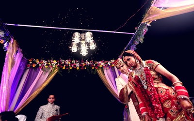 Vedi mandap decorated with pink, purple and gold drapes, and a mini chandelier lighting up the whole space