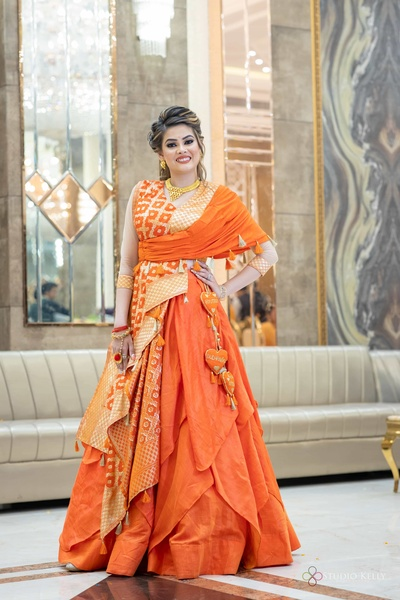 the bride looks absolutely gorgeous in her bright orange lehenga!