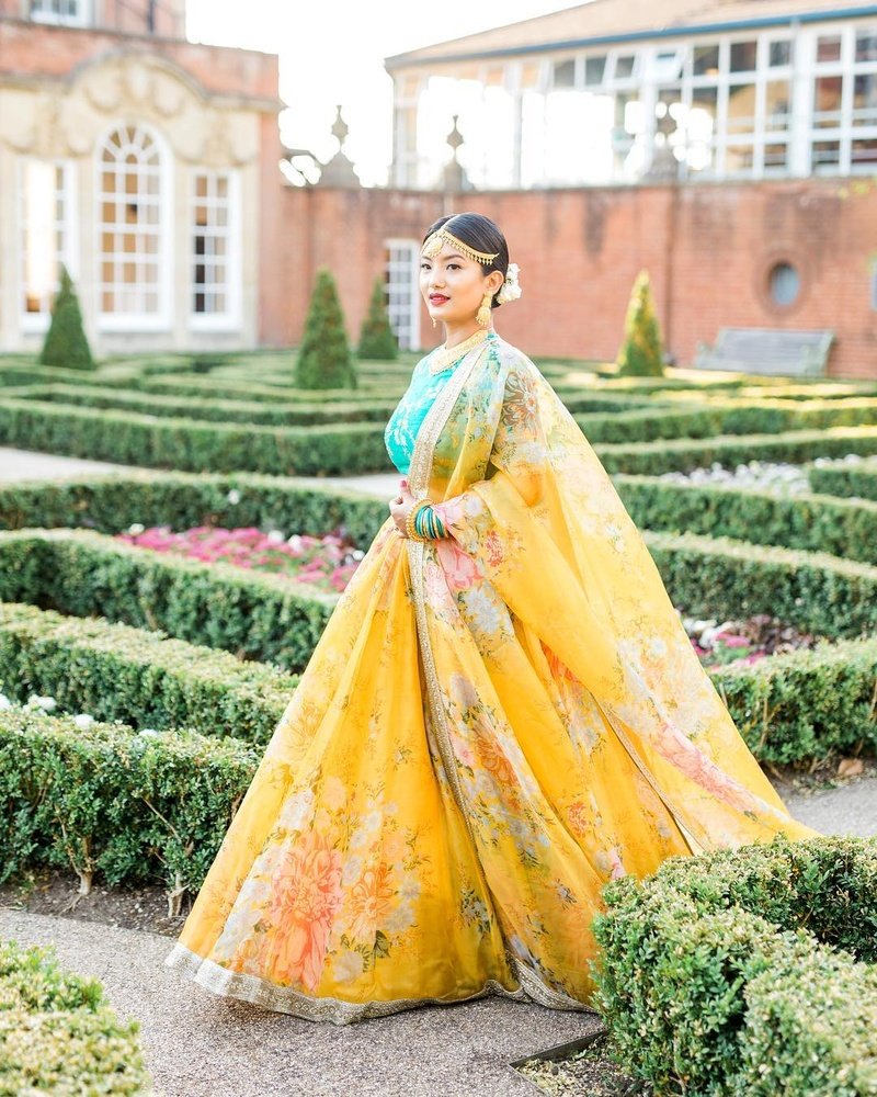 c13600c9dc Yellow floral print lehenga skirt and dupatta paired with a green choli: