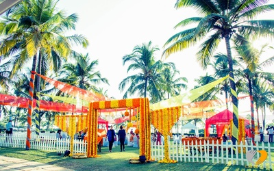 Wooden arch decorated in spiral and strings style arrangement of the orange and yellow Marigold flowers, Outdoor decor for the pre wedding celebrations