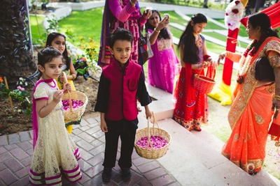 Cute kids at wedding holding flowers to welcome the bride.