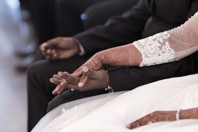 Francis and Ujwala holding hands during their wedding ceremony.