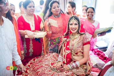 Bridal red lehenga styled with a matching sheer red dupatta embellished with a gold beaded border