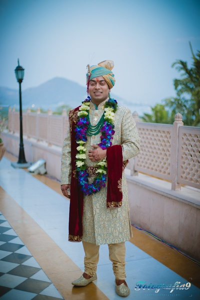 Powder blue and gold wedding sherwani embellished with resham embroidery, paired with a maroon sequined dushala