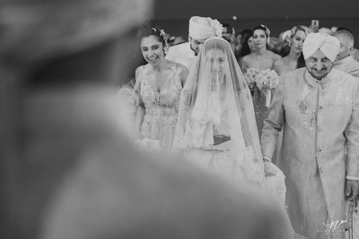 The bride walking towards the groom with her family in toe