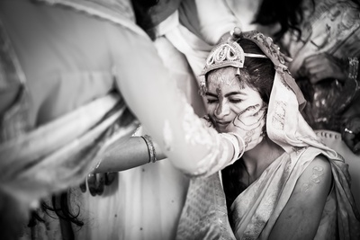 The bride is getting haldi all over her face!