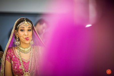 Bride Ratica strikes a quirky expression while getting ready for the wedding ceremony