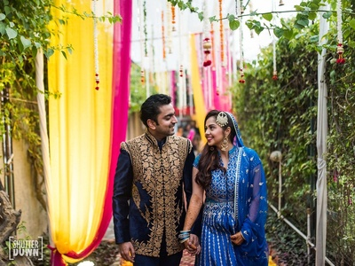 Candid capture of the bride and groom twinning in their blue outfits