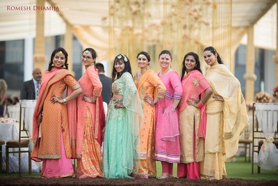 Bridesmaids dressed up in pastel shade outfits.