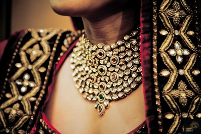Red and green bridal lehenga by Tarun Tahiliani styled with kundan studded bridal necklace set