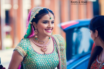 Green and pink wedding lehenga, styled with necklace set studded with stones, crystals and matching earrings and maangtikka