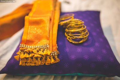 Mustard color saree from Chandini Collections in Malleswaram with gold bangles for the reception.